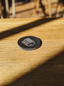 Bar Promotion Ideas; black beermats stacked on a wooden table