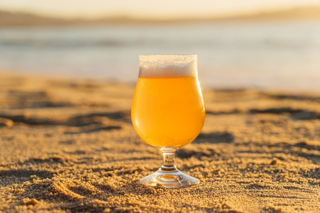 A glass of beer kept on the sand on a beach