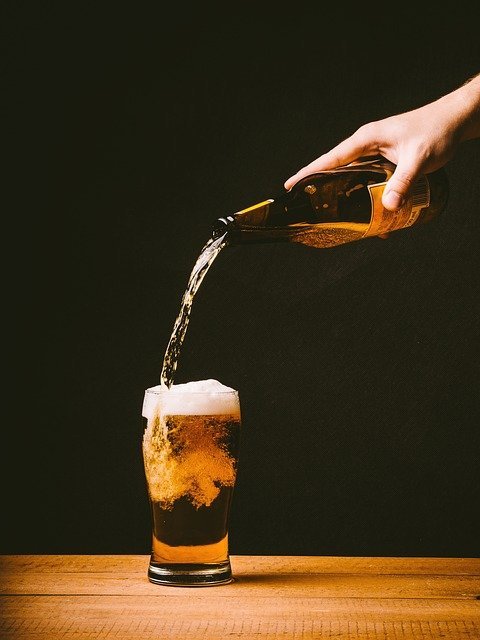 Craft Beers 2021; a person pouring beer into a glass placed on a wooden table