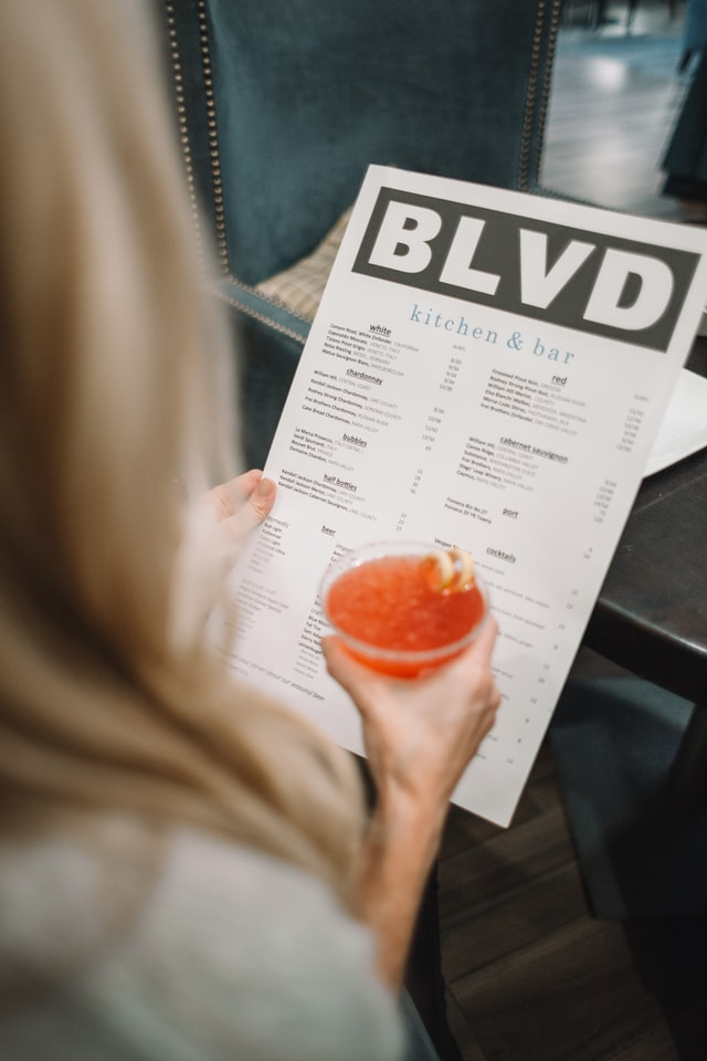 Offline Restaurant Marketing Ideas; a woman holding a beverage in her hand and reading a restaurant's menu