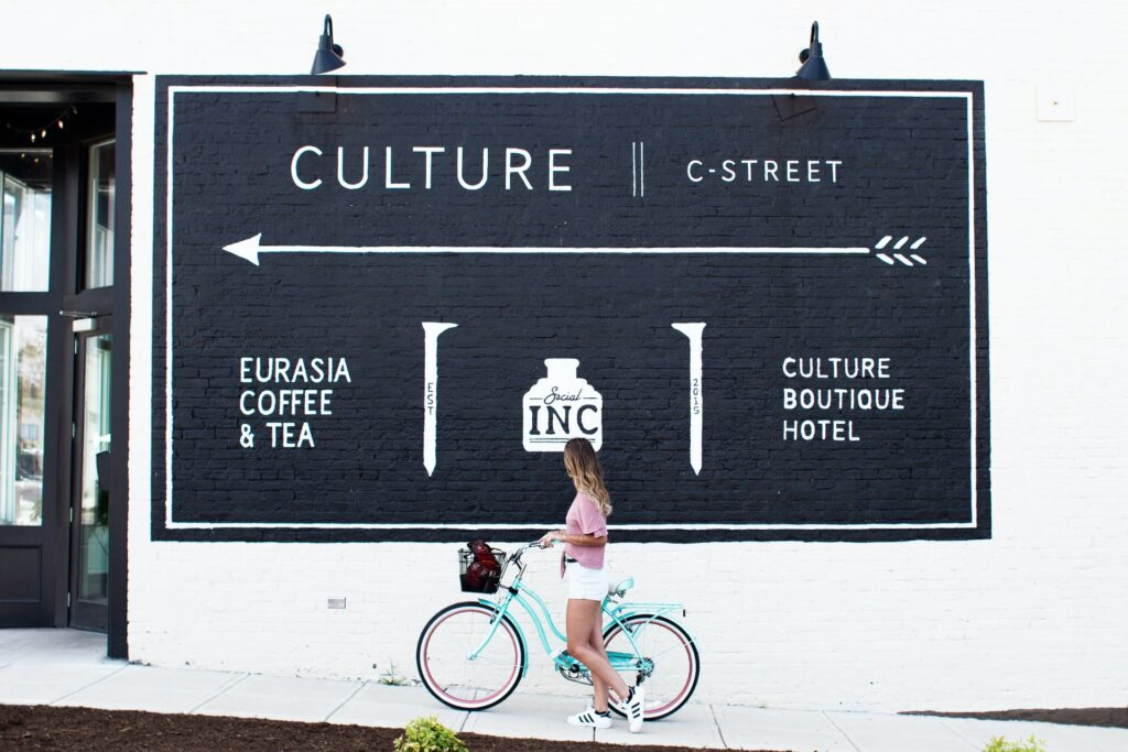 A young woman walking her bike past a billboard advertising coffee