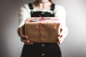 A person holding a nicely wrapped gift in their hand