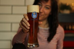 woman holding a glass full of beer