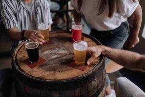 Unique uses of beermats; drinks placed over beermats on a wooden barrel