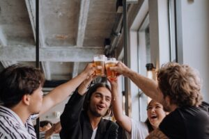 History of Craft Beer; A group of people clinking their beer glasses to one another.