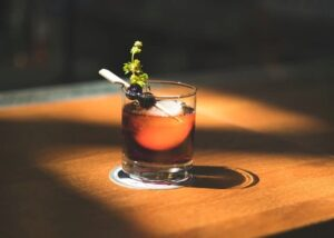 Beermat Finishing Options; an aesthetic glass of drink placed on a coaster on top of a wooden table
