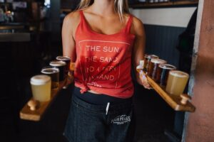 History of Craft Beer; A woman approaching to serve different kinds of beers in tasting glasses.