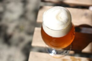 History of Craft Beer; An aerial view of a glass of foamed beer place on a wooden table.